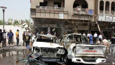 Iraq security forces and onlookers gather at the site of a car bomb attack in Baghdad on May 9, 2015, which killed seven civilians and wounded 14 others.