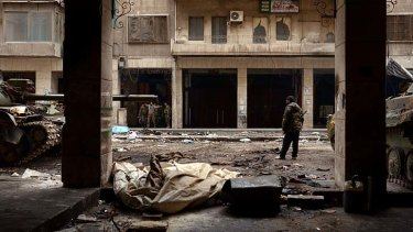 Vigilance amongst the rubble ... Syrian government forces patrol the streets of a district under their control in Aleppo.