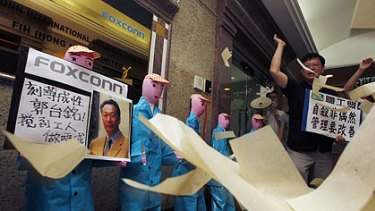 Protesters from several workers' rights groups throw paper money in front of paper figures, depicting workers who recently died in apparent suicides, during a traditional Chinese mourning ceremony outside a Foxconn office in Hong Kong.