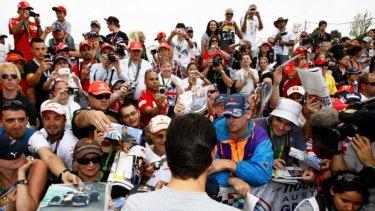 Australia's Mark Webber signs autographs for diehard fans including Brett Wheeler in blue jacket.