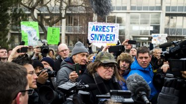 Filmmaker Michael Moore, who was born in Flint,  attends a rally outside City Hall, accusing Michigan Governor Rick Snyder of poisoning the city's water.