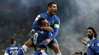 Jaw-dropping: Greece's Kostas Katsouranis, top, congratulates Kostas Mitroglou for his goal against Romania.