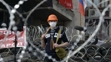 A pro-Russian protester stands at a barricade outside a regional government building in Donetsk.