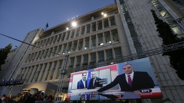 People watch the night news on a screen outside the state broadcaster ERT building following its re-launch after two years in Athens on Thursday.