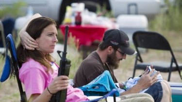 """Chris Shelton of Las Vegas interacts with his one-week-old son as his mother Shelley Shelton holds his rifle during a Bundy family """"Patriot Party"""" in Nevada."""