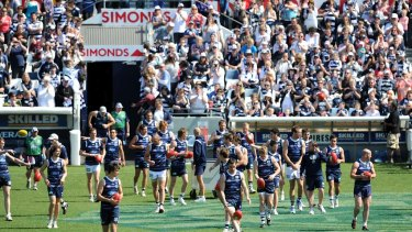 Geelong players make their way on to the ground in front of thousands of fans.
