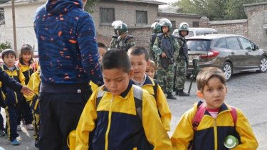 Children leave school under armed guard in Urumqi.
