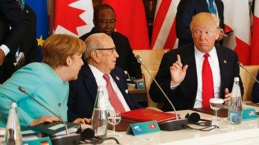 US President Donald Trump talks to German Chancellor Angela Merkel at the G7 summit.