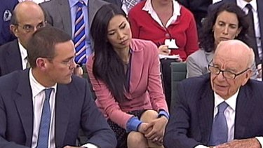 James (left) and Rupert Murdoch (right) answer questions from British politicians, with Rupert's wife Wendi (centre) watching on.