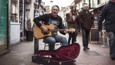 """Guitar man ... Neil Brooks busking in London """"making a few bob, putting food on the table""""."""