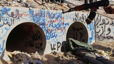 Last stand ... an anti-Gaddafi fighter points at the drain where Muammar Gaddafi was reportedly hiding before he was captured.