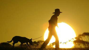 A farmer takes advantage of daylight saving to take his dog for a walk.