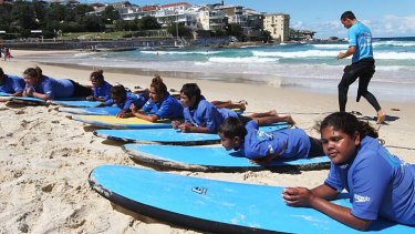 School's out: Aboriginal children learn to ride the surf at Bondi.