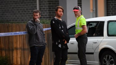 Two of Leonie Stuart's sons and her husband outside their home after the shooting in March.