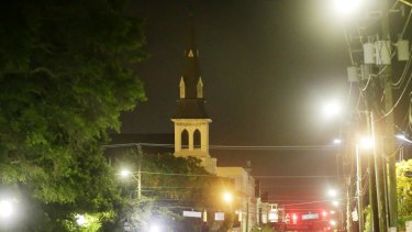 The steeple of Emanuel AME Church is visible as police close off the street after the shooting.