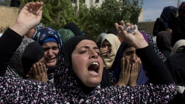 Palestinian mourners cry at the family house upon the arrival of the body of Amjad Jundi, 19, who was killed after stabbing a soldier on a bus in southern Israel.
