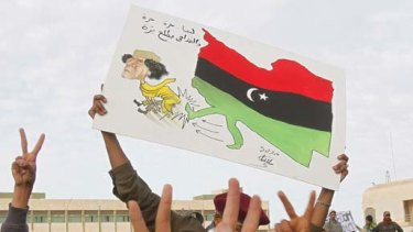 Protesters chant anti-government slogans while holding a banner depicting Libyan leader Muammar Gaddafi in Tobruk.