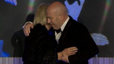 Breaking royal protocol? Flanagan hugs Camilla, Duchess of Cornwall, as he accepts his prize.