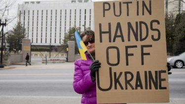 Taisia Bullard, who was born in central Ukraine, holds a protest banner in front in the Russian embassy in Washington.