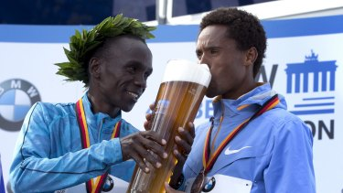 Bottoms up: Eliud Kipchoge feeds a beer to third placed Feyisa Lilesa.
