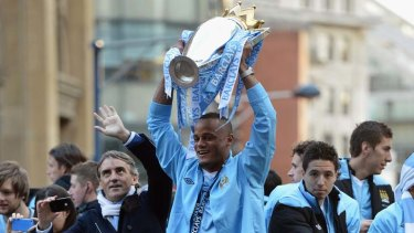 Jubilation: Manchester City captain Vincent Kompany (centre) and manager Roberto Mancini (left) celebrate with the team.