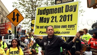 Proved wrong ... a person who believed the world was going to end carries a banner in New York.