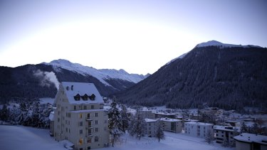 A blanket of snow covers the buildings and trees as the early morning light rises above the mountains in Davos, Switzerland, where world leaders, influential executives, bankers and policy makers will descend this week.