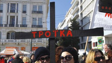 Frustrated … a demonstrator in Athens holds a black cross that reads ''Troika'', protesting the outside influences on the country.
