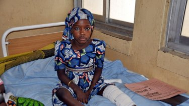 A child sits in state hospital as she receives treatment for injuries sustained following a bomb blast that left dozens dead and many injured in Maiduguri, Nigeria.