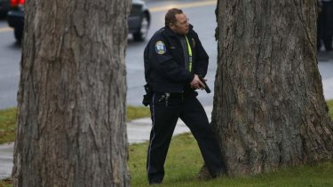 A police officer stands with his gun drawn outside the church.