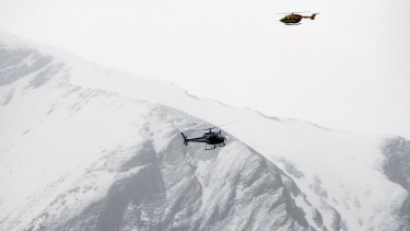 Rescue helicopters fly over the mountainside near Seyne-les-Alpes on Tuesday.