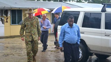 General Campbell, left, and Manus Island Police Chief  Alex N'Drasah, right, with immigration officials as they walk through the area where asylum seekers have been housed with criminals on Manus Island.