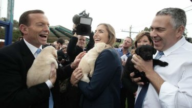 Opposition Leader Tony Abbott looks optimistic ahead of the polls during his visit to Guide Dogs Victoria with his daughter Frances Abbott, and shadow treasurer Joe Hockey.