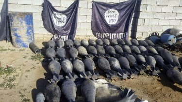 Weapons and explosives confiscated by Iraqi security forces from Islamic State militants on display at an Iraqi army base, with IS flags deliberately hung upside down as a mark of disrespect.
