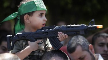 A Palestinian boy holds a toy gun as he participates in the Hamas rally.