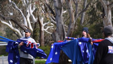 Protesters carry Australian flags to the Melton South rally.