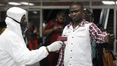 A Nigerian port health official uses a thermometer on a worker at the arrivals hall of Lagos airport.