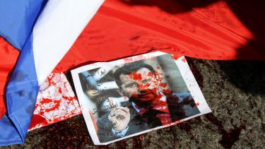 A picture of Syria's embattled President Bashar al-Assad sprayed with red paint lies on the ground.
