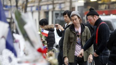 In this December 8 photo, members of the band Eagles of Death Metal, Jesse Hughes, right, and Julian Dorio pay their respects to 89 victims who died in the Novermber 13 attack at the Bataclan concert hall in Paris.