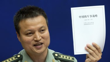 China's Defence Ministry spokesman Yang Yujun holds up China's Military Strategy white paper during a press conference in Beijing on Tuesday.
