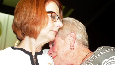 Julia Gillard is hugged after she offered the national apology for forced adoptions in the Great Hall at Parliament House on Thursday.