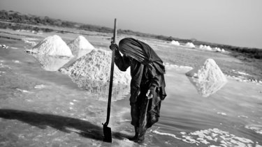 Bashia Mohammed gathers salt, surrounded by a sewer.