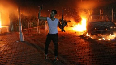 Fiery end: A man waves his rifle during the deadly attack.