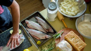 """""""Local"""" is overtaking organic as the must have label for food-conscious consumers. Preparing trout caught at the Tuki trout farm. The bread was baked at home from locally milled wheat."""