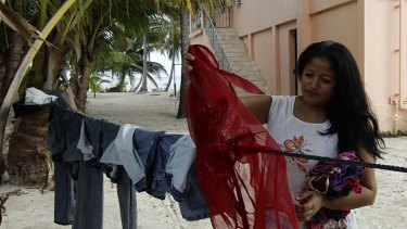 Reyna Galdamez, 24, an employee of dead American businessman Gregory Faull, collects clothes outside of Faull's home in San Pedro.