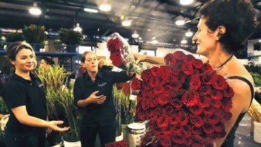 Love through rose-coloured glasses ... Parthenie Lalas, left, and Sarah Malone, centre, help their boss Tanya Waterhouse buy roses at the Flemington flower market.