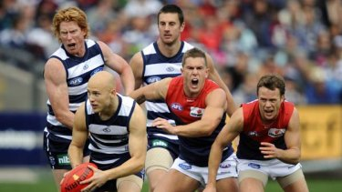Melbourne's Brent Moloney and James McDonald try to catch Geelong's Gary Ablett.