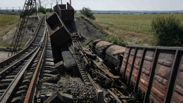 Train wagons on a destroyed railway bridge which collapsed during the fighting between the Ukrainian army and pro-Russian separatists.