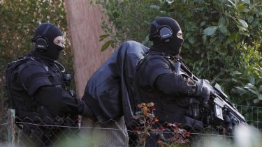 French special forces police make an arrest in Coueron, near Nantes as part of widespread raids.