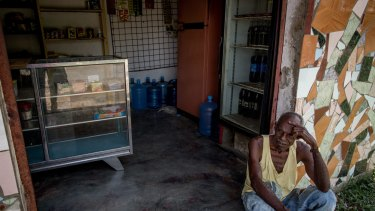 A man rests in front of a local store in Barlovento. The store has not received food since January, forcing people to go to bigger towns or even Caracas to shop.